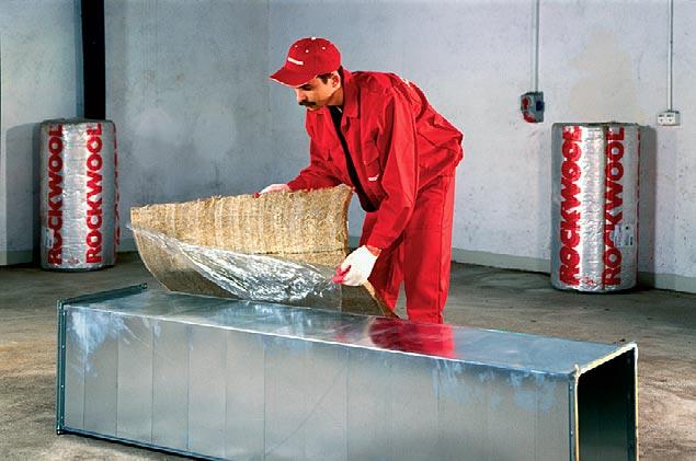 Fot. 5. Najpowszechniejszą metodą mocowania płyt i mat do kanałów wentylacyjnych jest ich klejenie bezpośrednio na powierzchnię przewodów. Warunkiem jest, by powierzchnia była sucha, czysta i odtłuszczona. W zdecydowanej większości materiały izolacyjne oferowane są z gotową warstwą kleju, która upraszcza montaż do minimum. Izolacja kanałów wentylacyjnych. Fot. ROCKWOOL